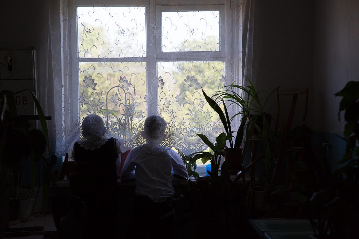Мальчишки наблюдают в окно за гоняющими мяч ребятами Медиапроект s-t-o-l.com