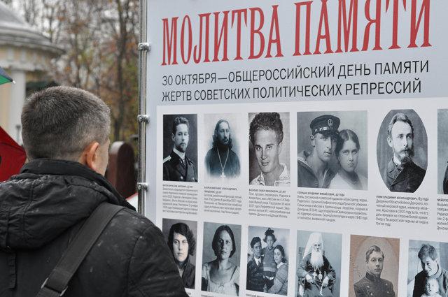 Мужчина рассматривает плакат акции Молитва памяти Медиапроект s-t-o-l.com